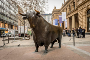 Frankfurt am Main, Germany - November 27, 2015: View of the bronze bull figure right outside the Frankfurt Stock Exchange building, along with people, vehicles, buildings and nature in Frankfurt, Germany