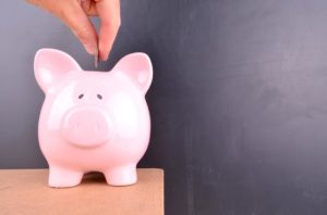 A coin is deposited into a pink piggybank with a blank blackboard in the background.