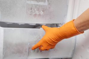 Hand in glove opening refrigerator.